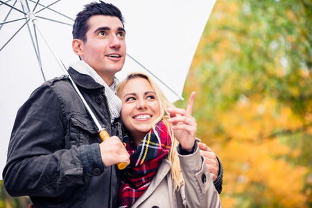 embracing couple: Couple enjoying fall day having walk despite the rain