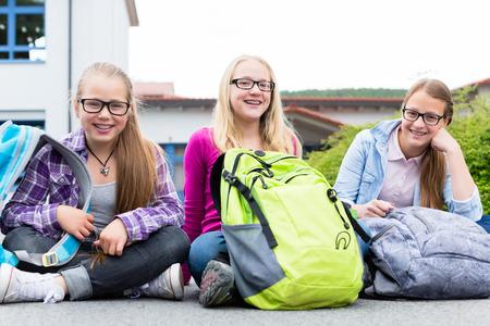recess: Schoolgirls sitting in schoolyard at school having recess and talking
