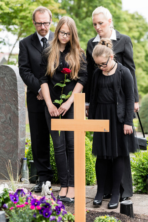 graves: Family mourning at grave on graveyard or cemetery