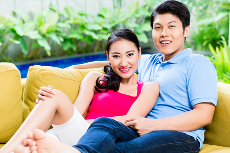 huddling: Chinese woman and man of sofa in their home Stock Photo