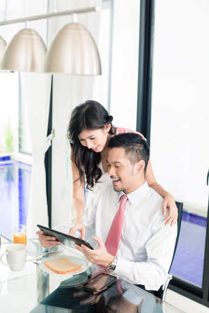 asian wife: Asian couple having breakfast before man goes to office, he is checking the emails or news with his wife Stock Photo