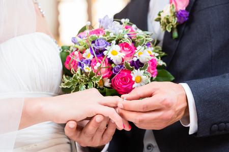 Groom glisser l'anneau sur le doigt de la mariée au mariage Banque d'images