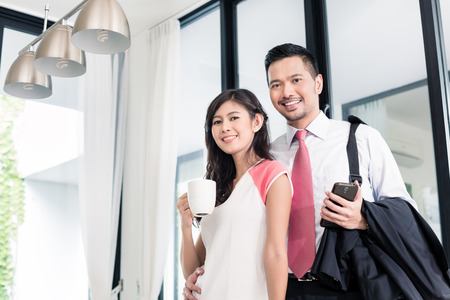 having breakfast: Asian couple having breakfast before man goes to office, standing in their home