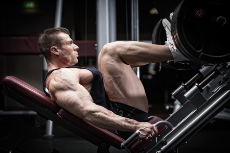 musculo: Hombre en el entrenamiento de gimnasia en prensa de piernas para definir sus m�sculos superiores de la pierna Foto de archivo