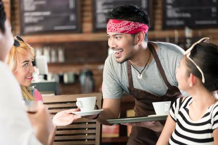 camarero: Camarero sirviendo caf� en caf� asi�tico para las mujeres y el hombre que ofrecen las bebidas en una bandeja Foto de archivo