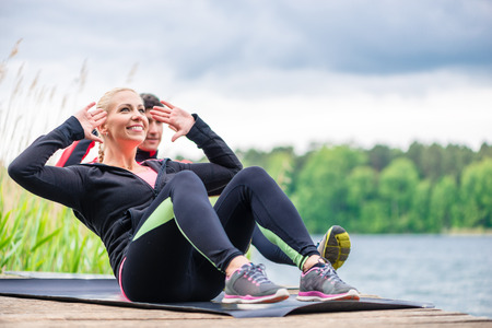 situp: Sport couple doing sit-ups outdoor at river