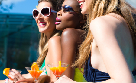 niñas en bikini: Tres mujeres amigos bebiendo cócteles en el bar piscina, africana y niñas de raza blanca