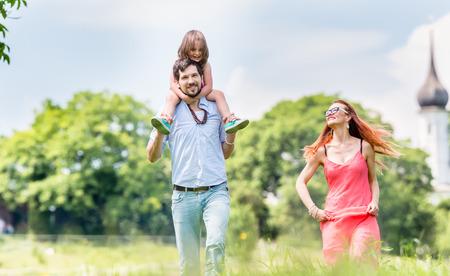 familia en la iglesia: Familia caminando en la pradera que tiene caminata, papá está llevando a su pequeña hija en los hombros