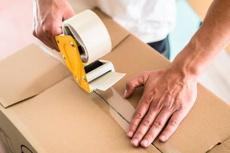 páska: Man taping přepravní bedna Reklamní fotografie