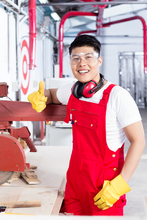 cabinet maker: Proud worker at his workplace in Asian industrial plant next to a production machine