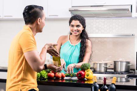 esposas: Mujer ind�gena y el hombre en la cocina con la ensalada de la elaboraci�n del vino rojo Foto de archivo