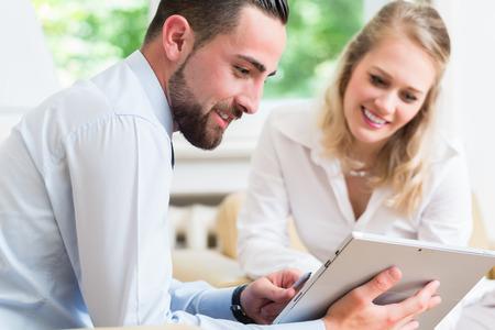 mujeres trabajando: Mujer y hombre de negocios en reunión de trabajo mirando a la presentación en el ordenador tableta