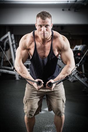 arm muscles: Bodybuilder doing butterfly on cable pull for better definition of his arm muscles