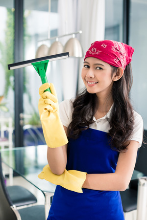 chore: Asian woman cleaning windows in her home enjoying the chore Stock Photo