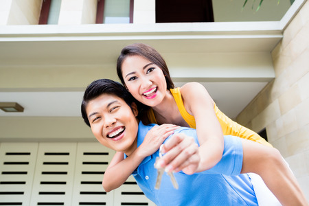 buying a home: Chinese man carrying his girl piggyback at new house, she is showing the home keys