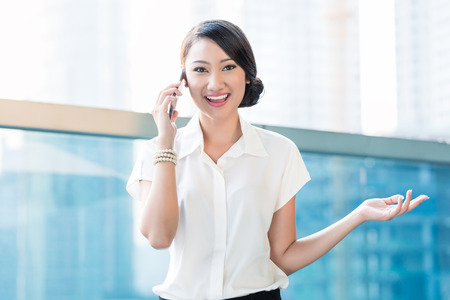 phone professional: Chinese Business woman in telephone call taken on terrace of office building outdoors Stock Photo