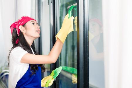 Aziatische vrouw reinigen van ramen in haar huis te genieten van het karwei Stockfoto
