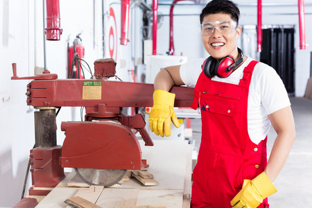 cabinet maker: Proud Chinese carpenter in his wood workshop standing next to an electrical circular saw