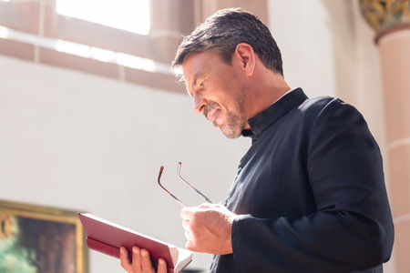 church: Catholic priest reading bible in church