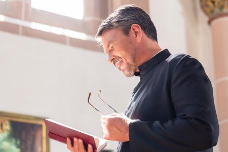 personas de pie: Sacerdote católico que lee la biblia en la iglesia