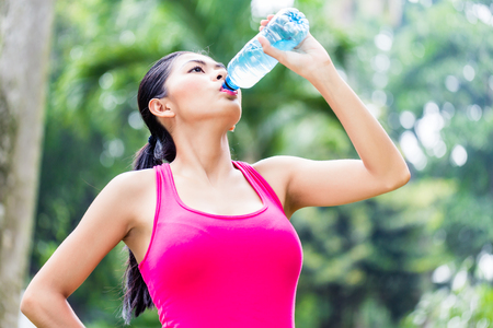 replenishing: Asian woman having break from sport training in tropical park, drinking water from a bottle Stock Photo