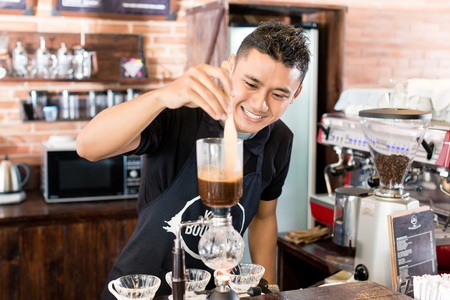 coffee bar: Barista preparing drip coffee in Asian coffee shop using professional machine parts