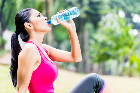 water park: Asian woman having break from sport training in tropical park, drinking water from a bottle Stock Photo