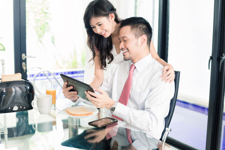 businessman in office: Asian couple having breakfast before man goes to office, he is checking the emails or news with his wife Stock Photo