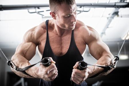 muscle: Bodybuilder que hace mariposa en cable de tracción para una mejor definición de sus músculos del brazo