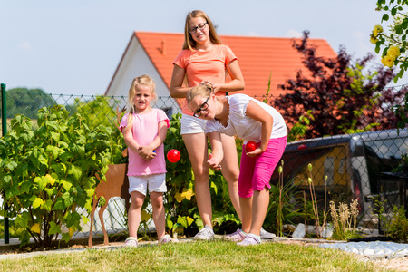 bocce: Three sisters playing bocce in garden front or their home in summer Stock Photo