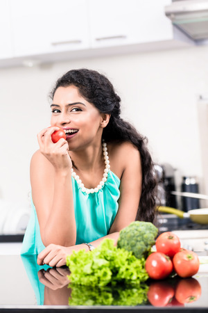 woman eating fruit: Indian woman eating healthy apple in her kitchen, salad and vegetables on the counter