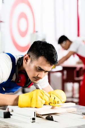 diligente: Trabajador diligente en la f�brica trabajando en la madera, en el fondo de su colega est� cortando un pedazo