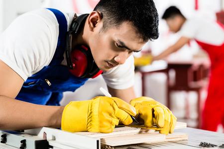 勤勉な労働者バック グラウンドで取り組んでいる木材の工場で彼の同僚が一枚を切っています。