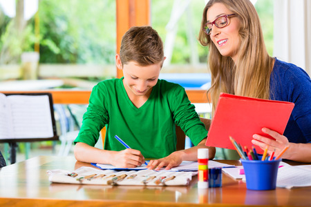 assignment: Mother helping son with homework assignment, painting a picture Stock Photo