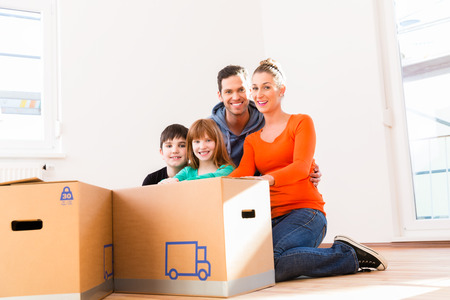 Family unpacking moving boxes in new home