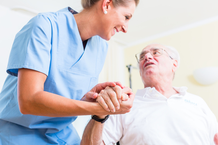 carer: Nurse holding hand of senior man in rest home