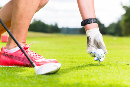 golfer: woman putting golf ball on tee, close shot