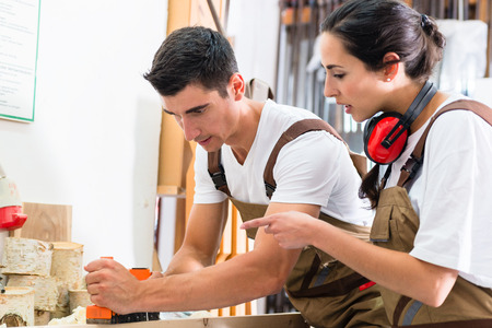 woodworking: Carpenter team of woman and man working together Stock Photo