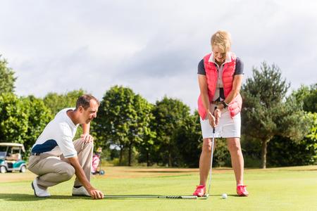 年配の女性とゴルフのプロのスポーツを練習
