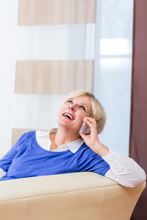 woman on phone: Senior woman phone at home sitting on couch
