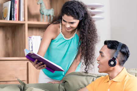 chilling: Indian wife showing her husband sitting on couch book she is reading Stock Photo