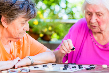 absorbed: Two senior ladies playing board game in rest home
