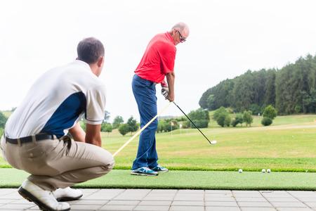 Golf trainer werken met golf speler op de driving range