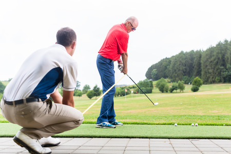golfer: Golf trainer working with golf player on driving range Stock Photo