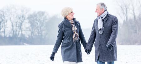 ancianos caminando: Pares mayores que tienen caminata en invierno