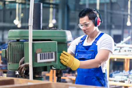 Asian worker in factory on drilling machine working on a piece of metal