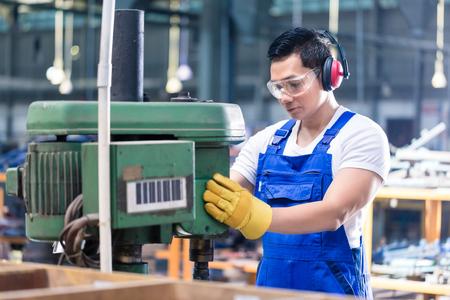 Operaio asiatico in fabbrica sulla macchina di perforazione a lavorare su un pezzo di metallo Archivio Fotografico