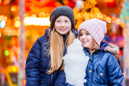 europeans: Children eating sweet candy on Christmas market