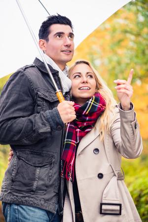 pareja abrazada: Pareja disfrutando día de otoño que tiene caminata pesar de la lluvia Foto de archivo