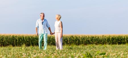 tercera edad: Pares mayores que tienen caminata en la pradera